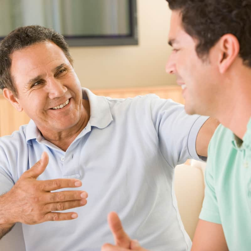 Man smiling at adult son, sitting next to each other on couch.