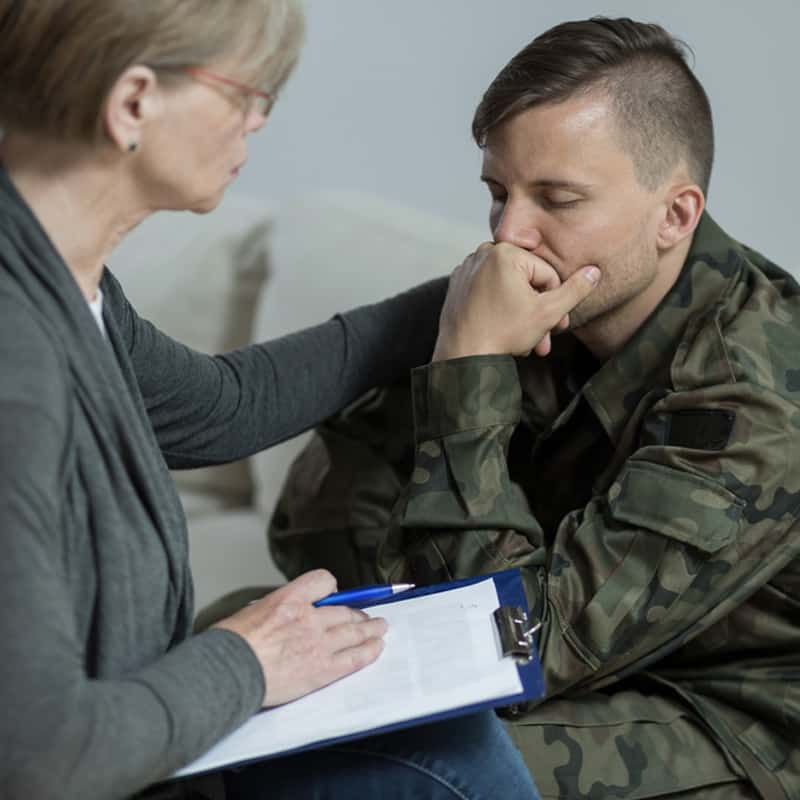 woman with clipboard comforting man in army fatigues