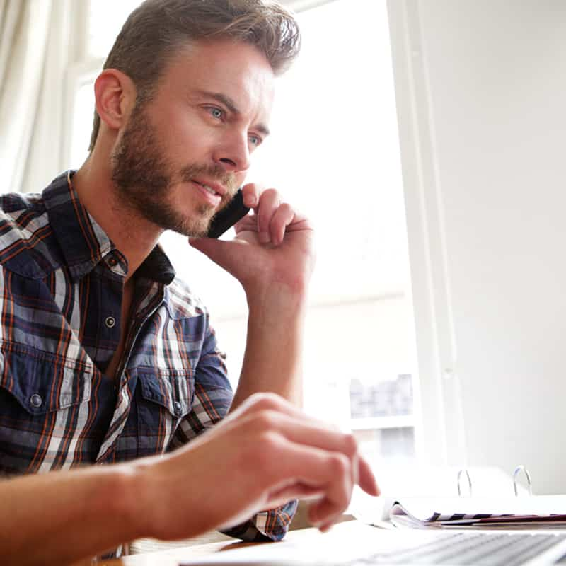 man in plaid shirt sitting at desk, talking on cell phone