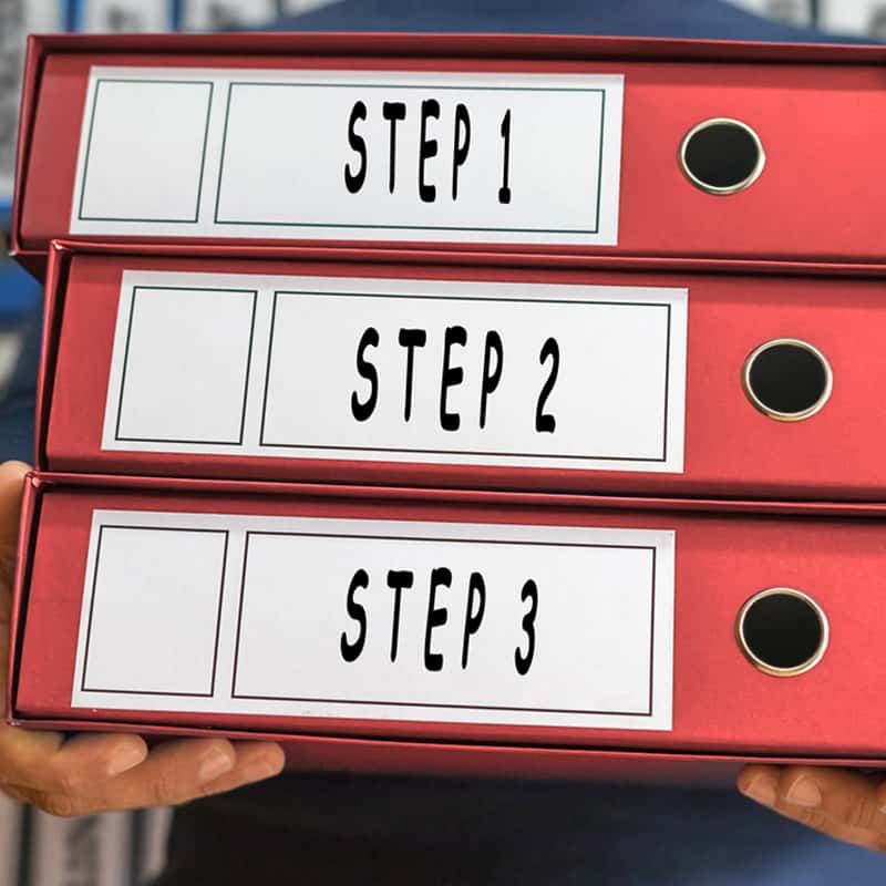 man holding red file holders that say Step 1, Step 2, and Step 3